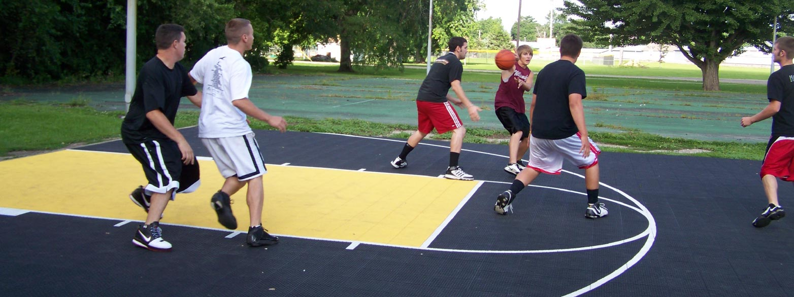Kids Playing Basketball on a black and yellow basketball court